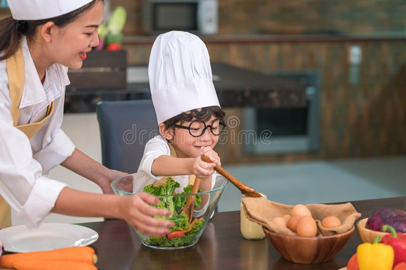 Happy beautiful Asian woman and cute little boy with eyeglasses prepare to cooking in kitchen at home. People lifestyles and royalty free stock images