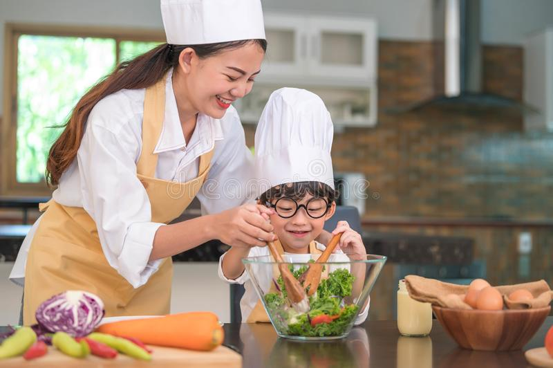 Happy beautiful Asian woman and cute little boy with eyeglasses prepare to cooking in kitchen at home. People lifestyles and stock photos