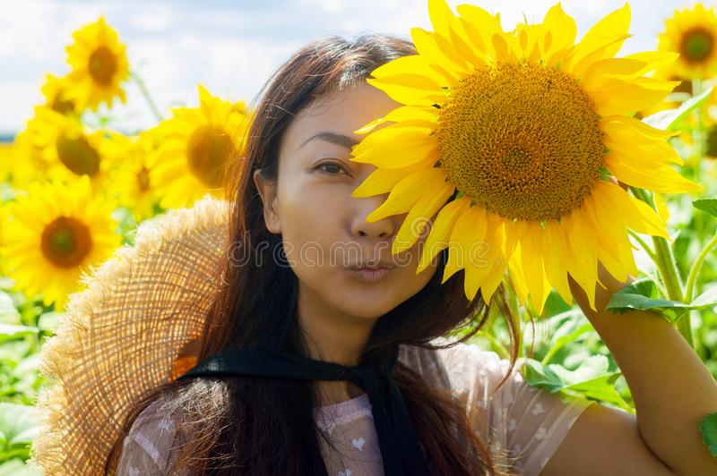 Happy beautiful asian woman with straw hat in sunflower field. royalty free stock photos