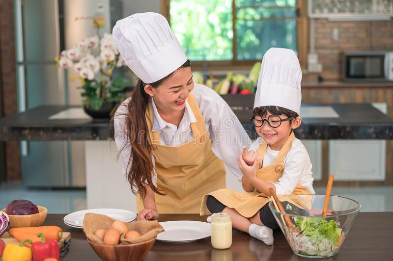 Happy beautiful Asian woman and cute little boy with eyeglasses prepare to cooking in kitchen at home funny. People lifestyles and stock photo
