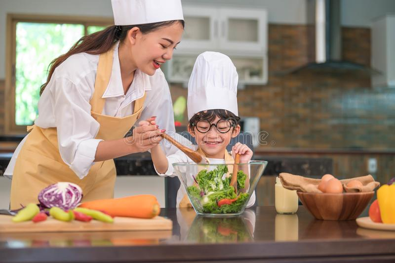 Happy beautiful Asian woman and cute little boy with eyeglasses prepare to cooking in kitchen at home. People lifestyles and royalty free stock photography