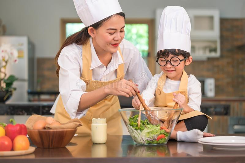 Happy beautiful Asian woman and cute little boy with eyeglasses prepare to cooking in kitchen at home. People lifestyles and stock photo