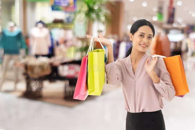 Happy beautiful Asian women smile two hand holding shopping bags royalty free stock image