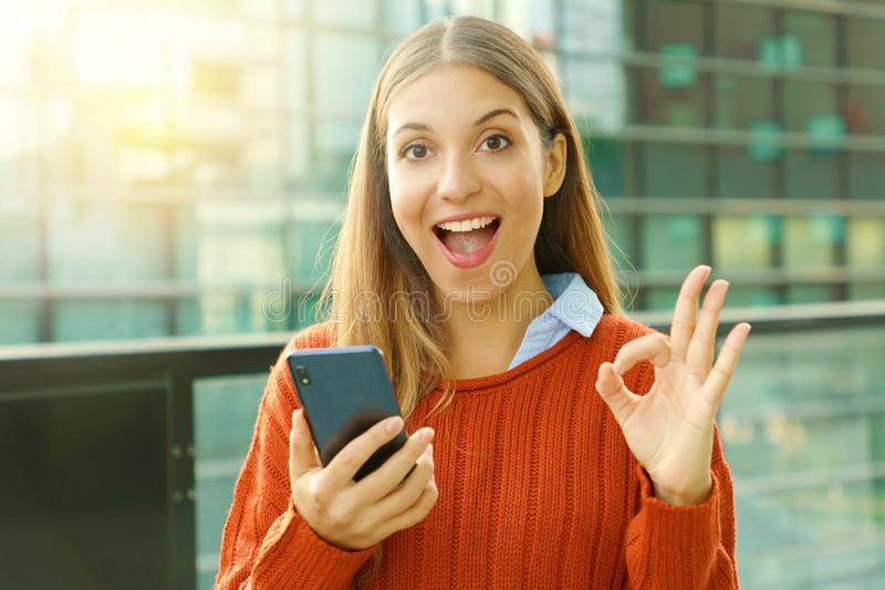 Happy beautiful autumn woman holding smart phone doing Ok sign at the camera. Excited satisfied young woman using smart phone stock photo