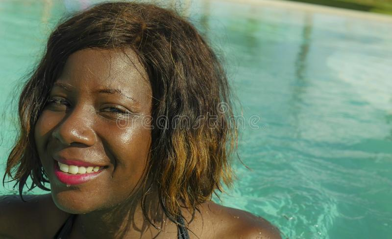 Happy and beautiful black afro American woman in bikini having fun at tropical beach resort swimming pool relaxed and playful. Young happy and beautiful black royalty free stock images