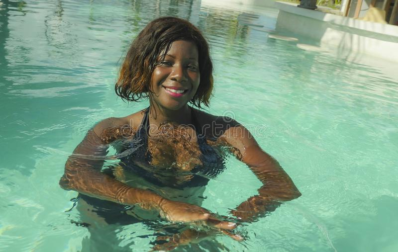 Happy and beautiful black afro American woman in bikini having fun at tropical beach resort swimming pool relaxed and playful. Young happy and beautiful black royalty free stock photo