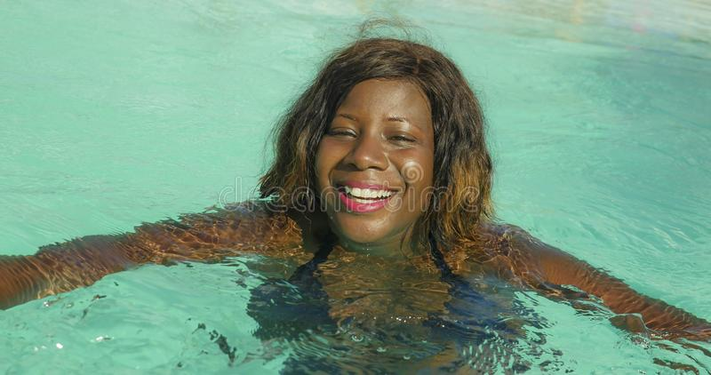 Happy and beautiful black afro American woman in bikini having fun at tropical beach resort swimming pool relaxed and playful. Young happy and beautiful black stock images