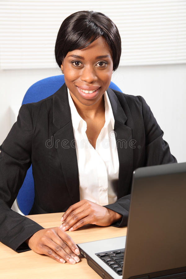 Happy beautiful black woman using laptop in office. Happy young black woman working in office sitting to her desk using her laptop, with a beautiful smile royalty free stock photo