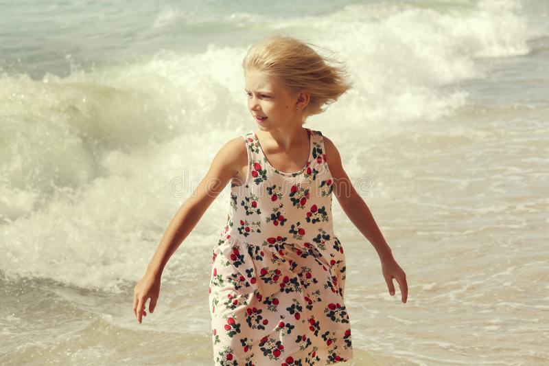 Happy and beautiful blond girl in a colored dress walking on the beach and looking at the waves. Vacation concept royalty free stock photography