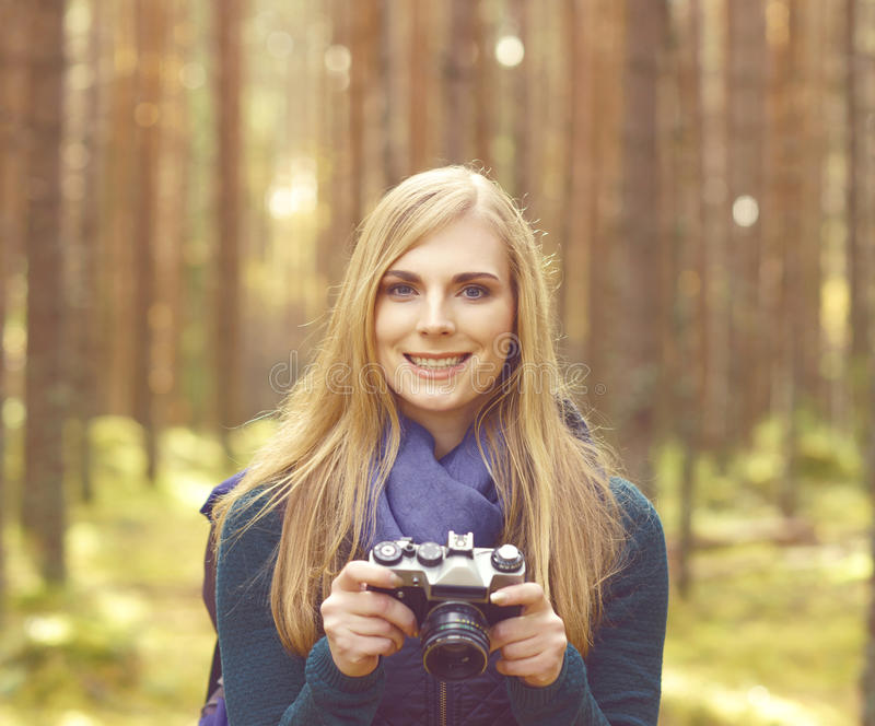 Happy, beautiful blond girl taking pictures in forest. Camp, tourism, hiking concept. stock images