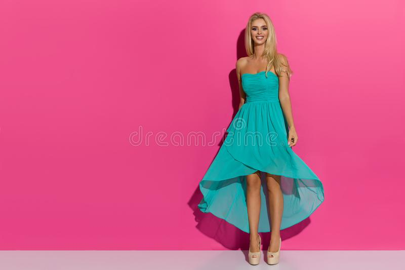 Happy Beautiful Blond Woman Posing In Turquoise Dress And High Heels royalty free stock photo