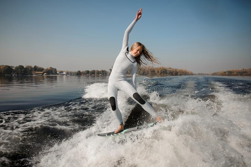 Happy blonde girl riding on the green wakeboard on the bending knees. Happy beautiful blonde girl in the white swimsuit riding on the green wakeboard on the royalty free stock image
