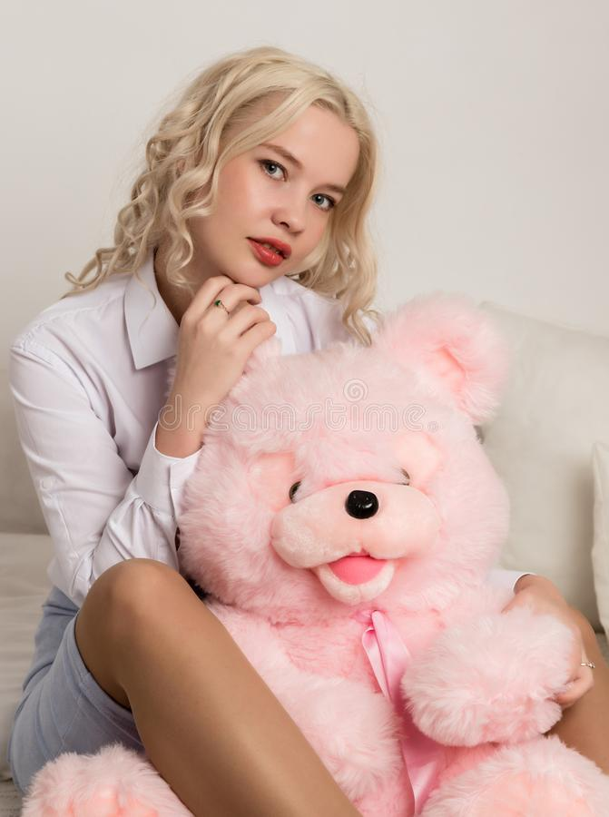 Happy beautiful blonde woman hugging a teddy bear. Concept of holiday or birthday.  stock photo