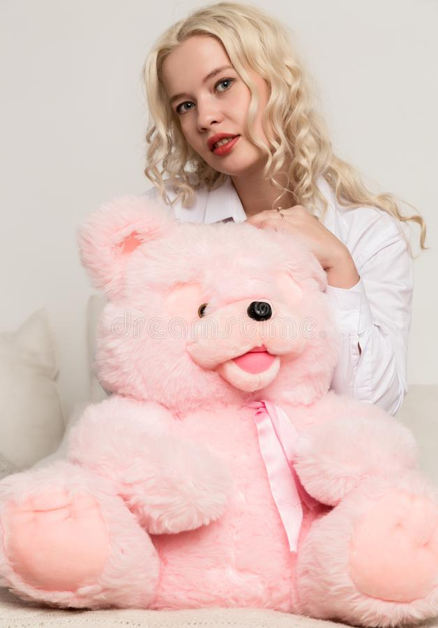 Happy beautiful blonde woman hugging a teddy bear. Concept of holiday or birthday.  royalty free stock images