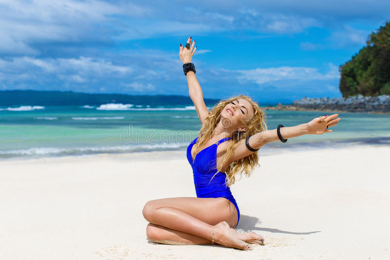 Happy beautiful blonde woman with long hair in a blue swimsuit o stock image