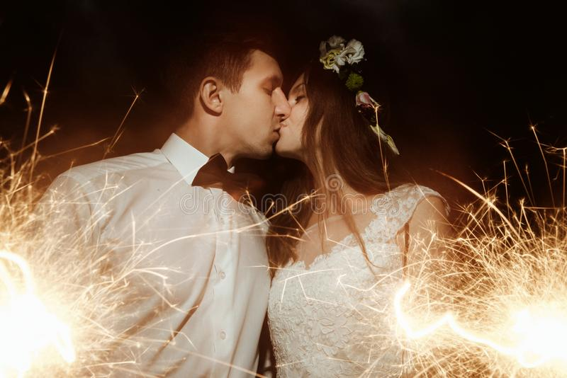 Happy beautiful bride and elegant stylish groom holding firework. S on the top of a mountains in the evening royalty free stock photos