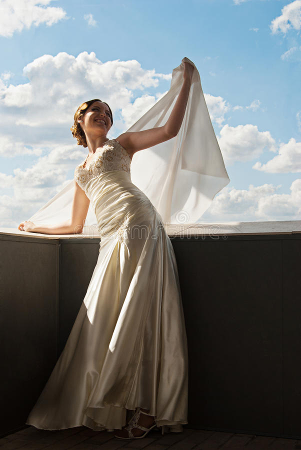Happy beautiful bride with flying fabric over sky. Portrait of happy beautiful bride with flying fabric over sky stock photography