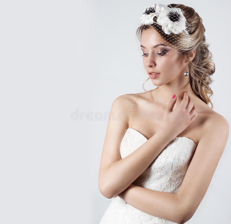 Happy beautiful bride woman blonde girl in a white wedding dress, with hair and bright make-up with veil in her eyes and flowers. In her hair in the Studio stock photo