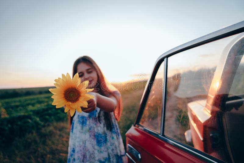 Happy beautiful brunette teen girl in dress with flowers print standing near red car among the field and pointing royalty free stock image