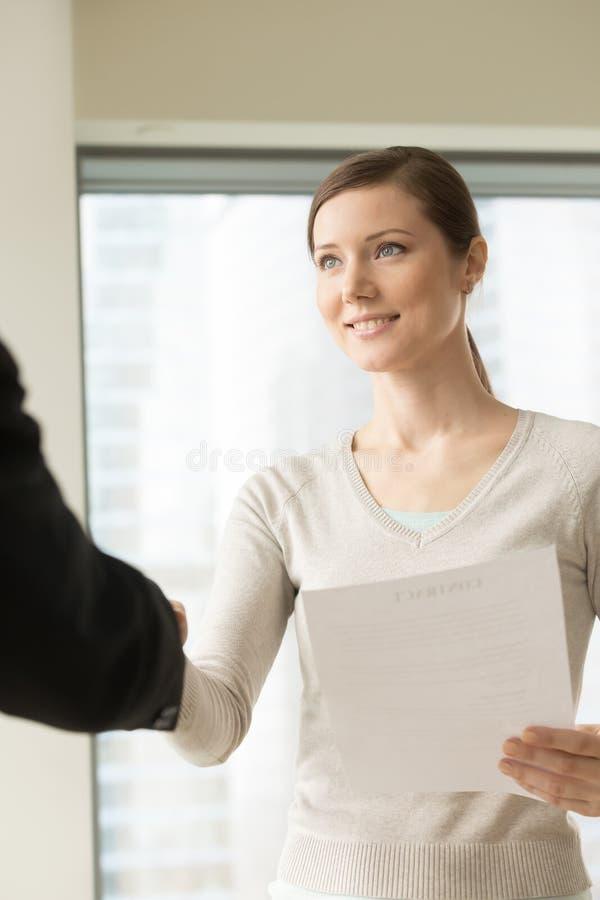 Happy beautiful businesswoman shaking businessman hand, holding stock photo