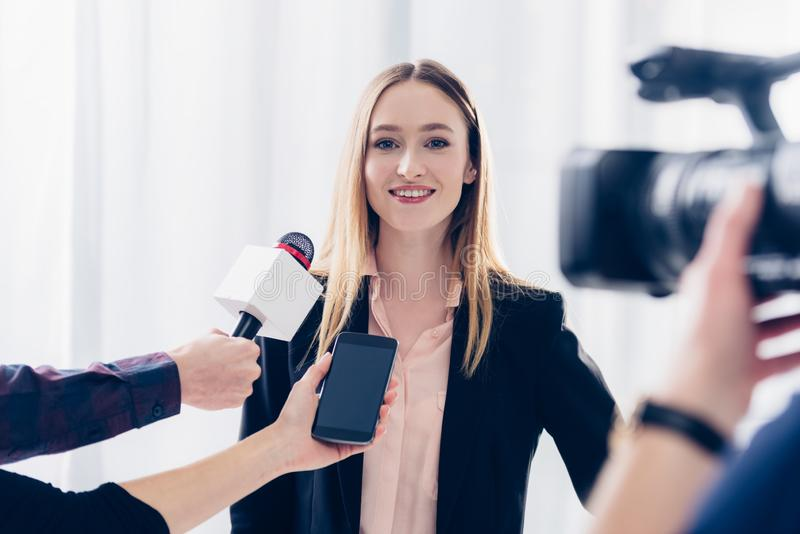 Happy beautiful businesswoman in suit giving interview to journalists. In office stock images
