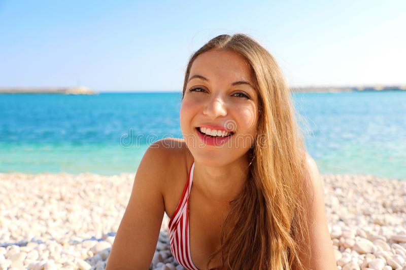 Happy beautiful cheerful smiling woman enjoying relax lying on the beach looking at camera. Summer holidays concept stock photos