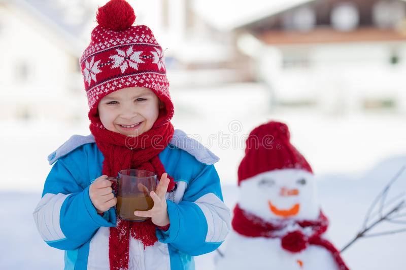 Happy beautiful child building snowman in garden, winter time, h. Olding cup of hot tea, smiling at camera stock image