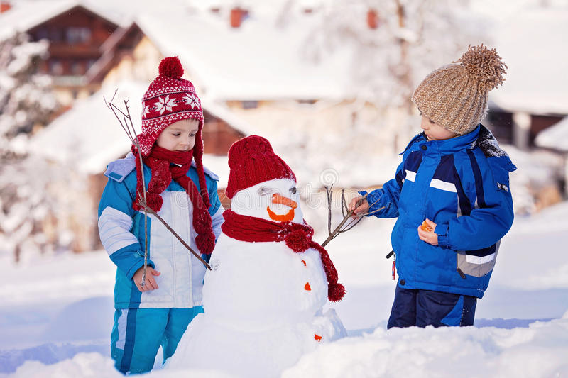 Happy beautiful children, brothers, building snowman in garden, royalty free stock photography