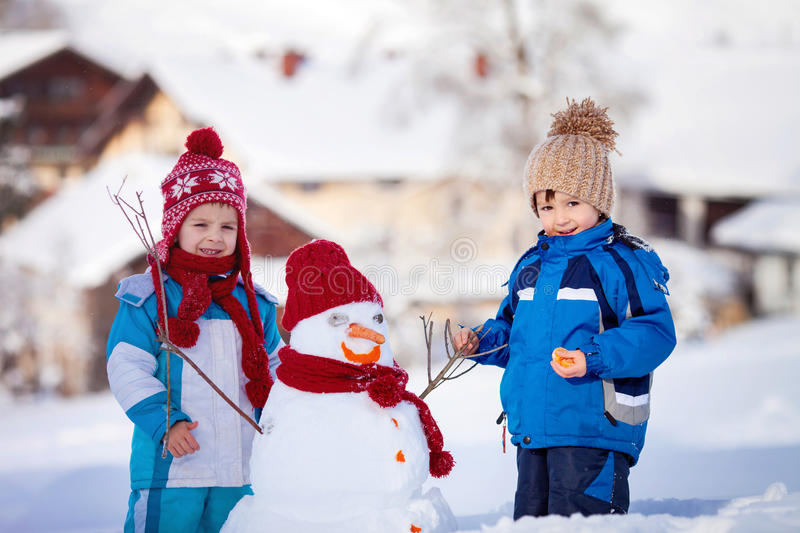 Happy beautiful children, brothers, building snowman in garden, royalty free stock photos
