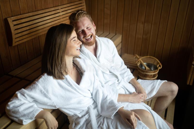 Happy couple enjoying the sauna together at the spa royalty free stock image