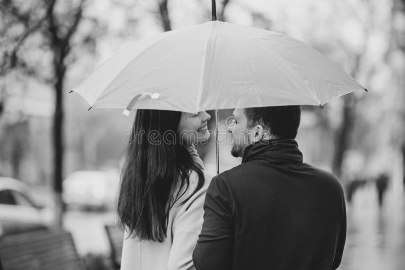 Happy beautiful couple, guy and his girlfriend dressed in casual clothes stand under the umbrella and look at each other stock photography