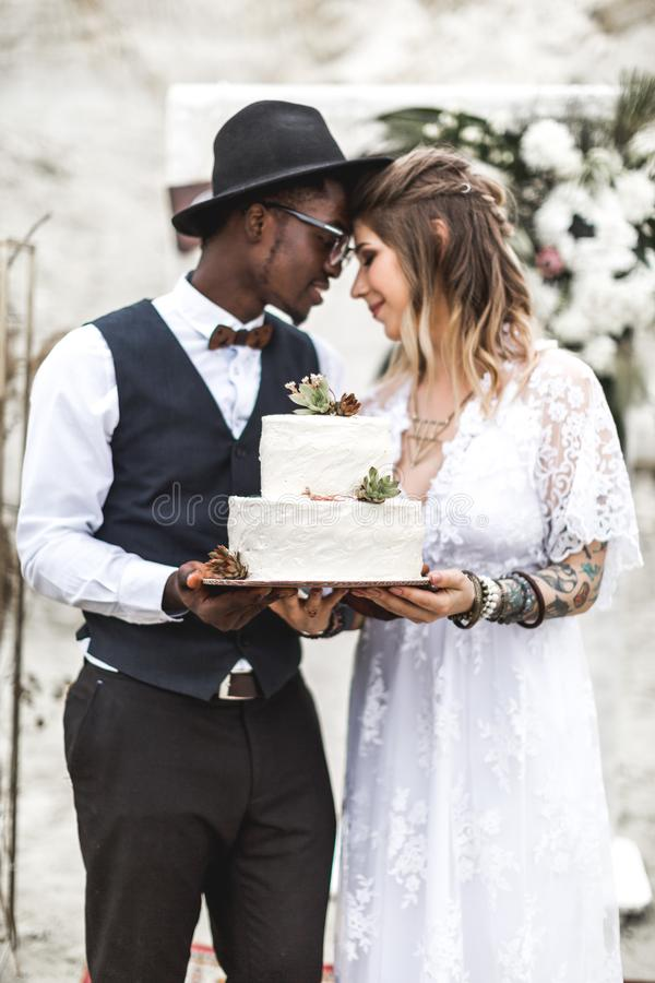 Happy beautiful couple have fun with wedding cake decorated with succulents in rustic style. Boho wedding stock photo
