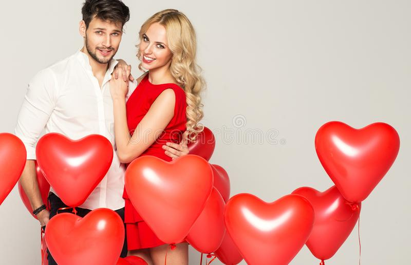 Happy beautiful couple looking at each other and holding balloons heart. Valentine`s day royalty free stock image