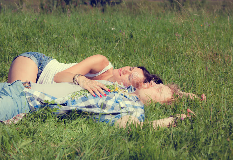 Happy beautiful couple in love lying on the green grass meadow. Happy beautiful couple in love lying on the green grass summer meadow royalty free stock image