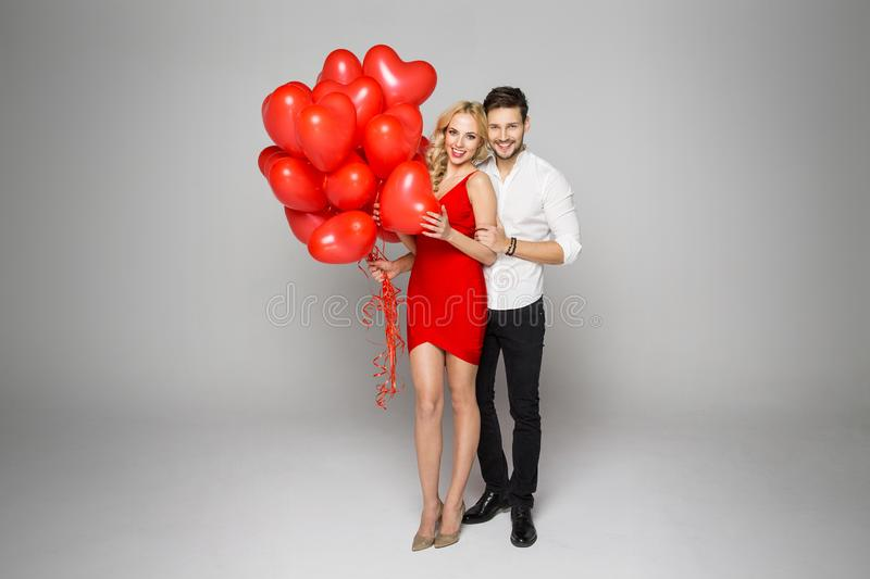 Happy beautiful couple holding balloons heart. Valentine`s day stock images