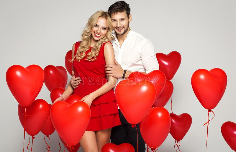 Happy beautiful couple looking at each other and holding balloons heart. Valentine`s day stock image