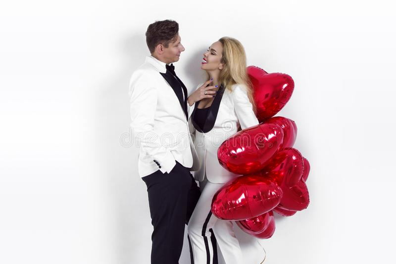 Happy beautiful couple posing on white background and holding balloons heart. Valentine`s day. royalty free stock image