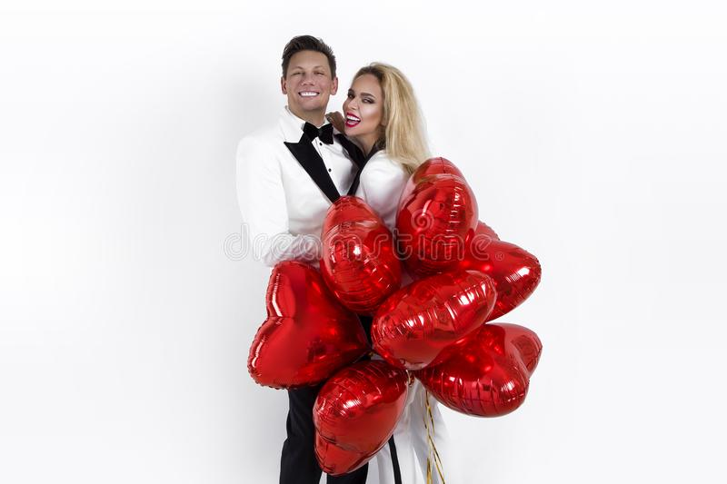 Happy beautiful couple posing on white background and holding balloons heart. Valentine`s day. stock image