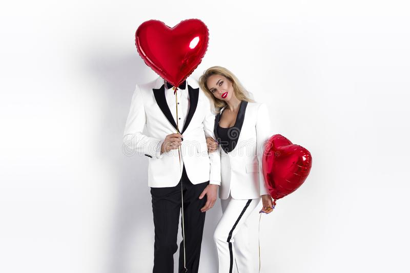 Happy beautiful couple posing on white background and holding balloons heart. Valentine`s day. royalty free stock photography