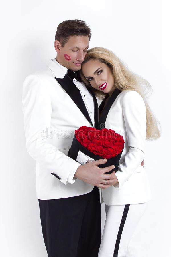 Happy beautiful couple posing on white background and holding flower box with red heart. Valentine`s day, wedding. Happy beautiful couple posing on white stock photos