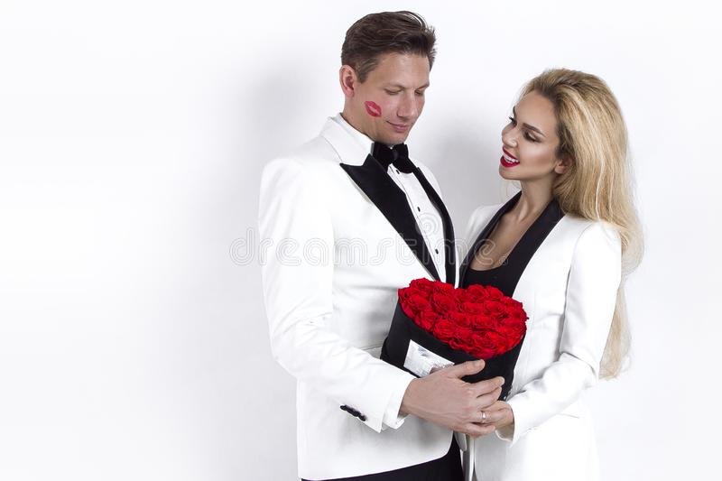 Happy beautiful couple posing on white background and holding flower box with red heart. Valentine`s day, wedding. Happy beautiful couple posing on white stock image