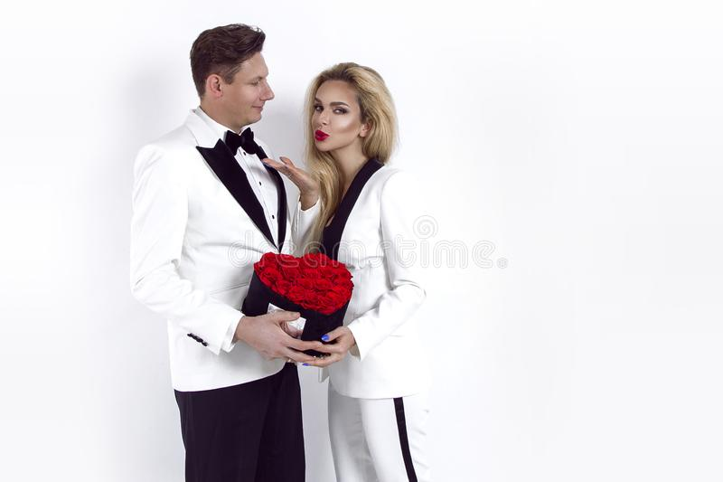 Happy beautiful couple posing on white background and holding flower box with red heart. Valentine`s day, wedding. royalty free stock photography