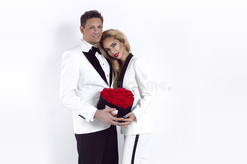 Happy beautiful couple posing on white background and holding flower box with red heart. Valentine`s day, wedding. stock photography