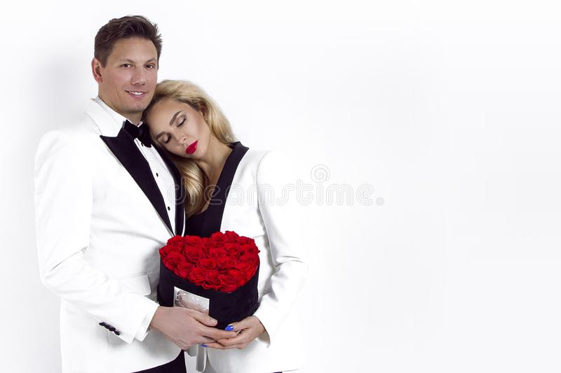 Happy beautiful couple posing on white background and holding flower box with red heart. Valentine`s day, wedding. stock photo
