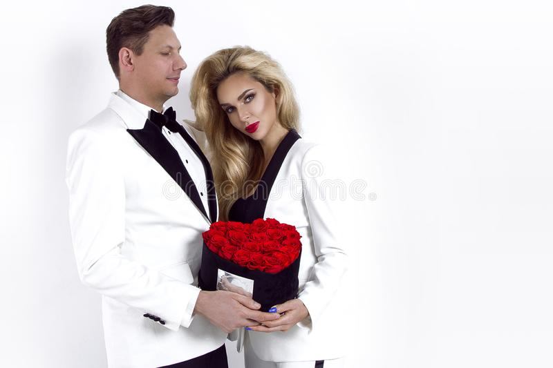 Happy beautiful couple posing on white background and holding flower box with red heart. Valentine`s day stock photo