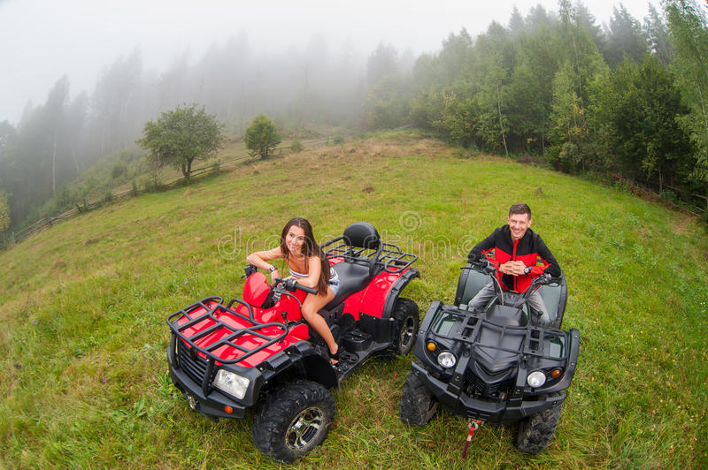 Happy beautiful couple sitting on four-wheelers ATV. In foggy nature. Smiling and looking to the camera. Wide view from high piont stock photo