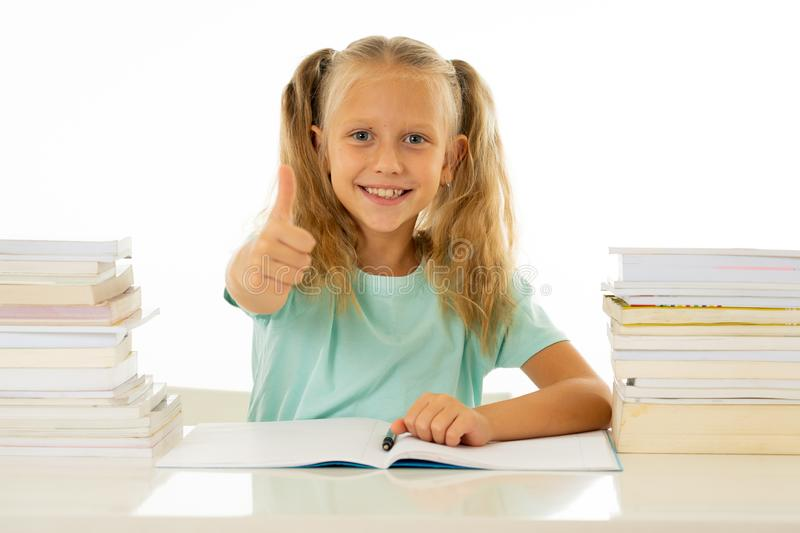 Happy beautiful cute with blond hair little schoolgirl likes studying and reading books in creative education concept with Back to. School theme isolated on stock images