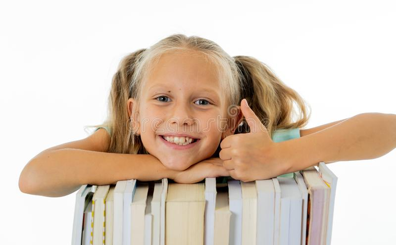 Happy beautiful cute with blond hair little schoolgirl likes studying and reading books in creative education concept with Back to. School theme isolated on stock image