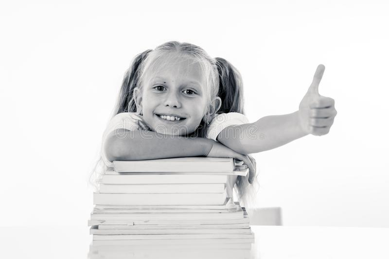 Happy beautiful cute with blond hair little schoolgirl likes studying and reading books in creative education concept with Back to. School theme isolated on stock photography