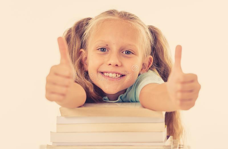 Happy beautiful cute with blond hair little schoolgirl likes studying and reading books in creative education concept with Back to. School theme isolated on royalty free stock images